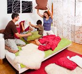 a young family is making a pillow-fight in their bedroom