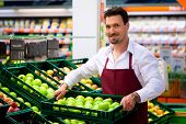 stock photo of supermarket  - Man in supermarket as shop assistant - JPG