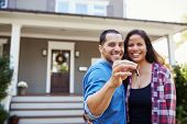 Portrait Of Couple Holding Keys To New Home On Moving In Day poster