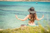 Young Woman In Green Swimsuit And Black Hat Practices Yoga On The Beach Of The Mediterranean Sea. Qi poster