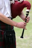 pic of bagpiper  - close up of young man playing the bagpipes - JPG