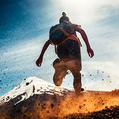 Woman athlete runs on a dirty and dusty ground with volcano on the background. Trail running athlete poster