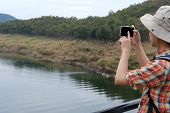 Traveler Man With Backpack Travel At Forest & Lake. Tourist Backpacker Use Smart Phone To Take Photo poster