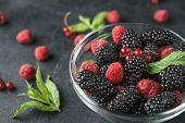 Glass Plate With Ripe Red Blackberries, Raspberries, Currant And Green Mint Leaves On A Black Surfac poster