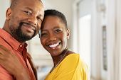 Portrait of romantic mature couple embracing and looking at camera. Smiling black man and woman toge poster