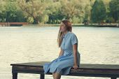 Young And Beautiful Girl Is Sitting On The Pier. The Pensive Look, Gazing Into The Distance poster