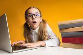 School Overload. Shocked Elementary Student Girl Doing Homework On Laptop Computer On Yellow Studio  poster