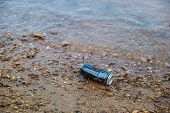 A Discarded Used Beverage Can Dumped On The Beach Near The Water At The Lake In Summer Polluting The poster