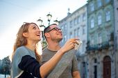 Happy Young Tourists Couple Holding A Paper Map Of Ancient European City Early In The Morning On Emp poster