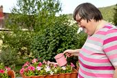 Mental Disabled Woman Is Watering Some Flowers In Her Outdoor Garden poster