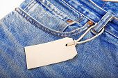 stock photo of hackney  - unbuttoned blue jeans with paper label isolated on white background - JPG