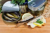 Smoked Sprats In Cooking Oil In The Open Tin Can, Two Open Sandwiches With Sprats And Lemon Against  poster