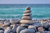 Zen meditation relaxation concept background - balanced stones stack close up on sea beach poster