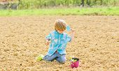 Gardening Concept. Child Having Fun With Little Shovel And Plant In Pot. Planting In Field. Planting poster