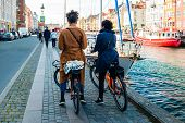 Two Girls On Bikes At Nyhavn Pier In The Old Town Of Copenhagen, Denmark. poster