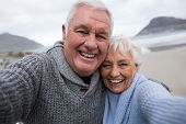 Portrait of smiling senior couple standing on the beach poster