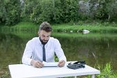 Businessman Reading Agreement Before Signing It. Concentrated Bearded Young Man Or Guy Attentively R poster