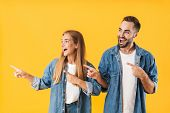 Image of pleased couple man and woman in denim clothes smiling while pointing fingers aside at copys poster