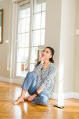 Young beautiful woman thinking and wondering with a hand on chin sitting on the floor at home poster