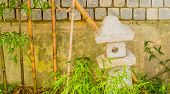 Small Cement Spirit House In Front Of Concrete Wall Next To Young Bamboo Plants. poster