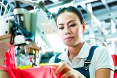 stock photo of sewing  - Seamstress or worker in a factory sewing with a industrial sewing machine - JPG