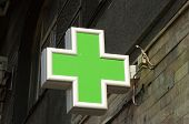stock photo of building relief  - Green light pharmacy sign on the street - JPG