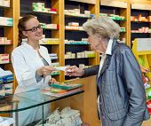 stock photo of over counter  - Smiling attractive young female pharmacist serving a senior lady over the counter dispensing her prescription medication - JPG