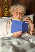 image of nightgown  - Elderly woman in her nightgown wearing glasses sitting propped up against the pillows reading a hardcover book in bed - JPG