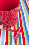 Stripy Beach Towel Red Bucket And Rake.