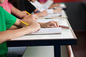 stock photo of schoolgirls  - Midsection of high school students writing on paper at desk in classroom - JPG