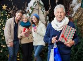Portrait of cheerful man holding Christmas presents and shopping bags with family standing in backgr
