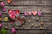 stock photo of small-flower  - Word Love with heart shaped Valentines Day gift box on old vintage wooden plates - JPG