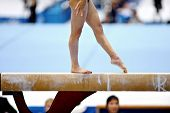 foto of gymnastics  - Legs of a gymnast are seen during an exercise on the balance beam apparatus