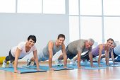 stock photo of senior class  - Fitness group doing push ups in row at the yoga class - JPG