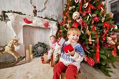 Little boy and little girl sit on big gift boxes under Christmas tree, holding open gift boxes of sm