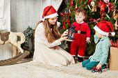 Three children sit on furry rug under Christmas tree, examining lantern poster