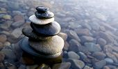 stock photo of zen  - Zen Balancing Rocks on Pebbles Covered With Water - JPG