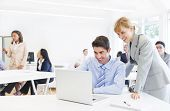 image of supervision  - Business Woman Supervising an Employee Working On a Laptop - JPG