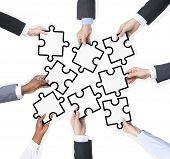 Group Of Business People Holding Pieces Of Jigsaw Puzzle