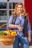 stock photo of vivacious  - Beautiful vivacious woman shopping for groceries standing in front of a supermarket with a basket of fresh fruit and vegetables over her arm