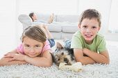picture of yorkshire terrier  - Siblings lying on rug with yorkshire terrier smiling at camera at home in the living room - JPG