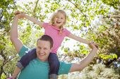 picture of piggyback ride  - Cute Young Girl Rides Piggyback On Her Dads Shoulders Outside at the Park - JPG