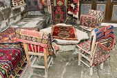 foto of goreme  - turkish carpets and leather handbags thrown over wooden furniture on display at a shop in Goreme Turkey - JPG