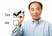 pic of yes  - Asian man checks YES on yes or no check list - JPG