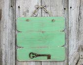 stock photo of skeleton key  - Blank green sign with bronze antique skeleton key hanging on weathered wood background - JPG