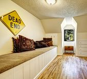 picture of vault  - Bench with carpet cover and brown pillows in empty room with vaulted ceiling - JPG