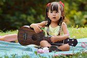 pic of ukulele  - Little asian girl was playing ukulele happily in the park - JPG