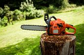 stock photo of chainsaw  - Chainsaw on a wooden stump - JPG