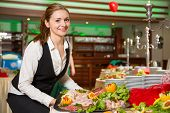 stock photo of buffet lunch  - Catering service employee or waitress preparing a buffet - JPG