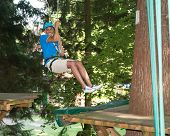 foto of ropeway  - Man sliding on ropeway at high rope course - JPG
